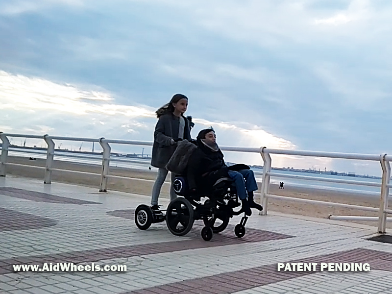 pushing wheelchair with hoverboard